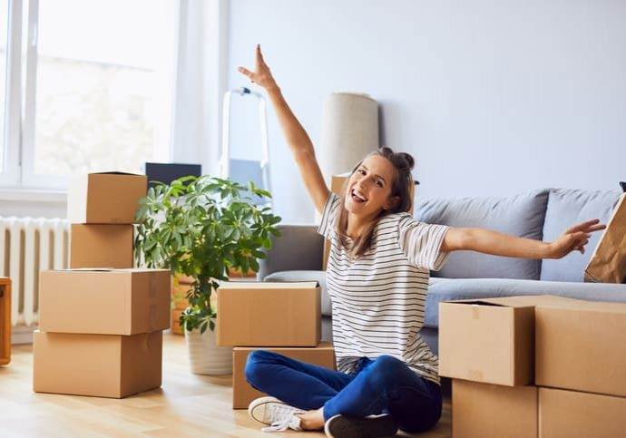 Young woman sitting in new apartment and raising arms in joy after moving in