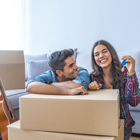 Cheerful and happy young couple holding the keys of their new home with moving cardbox during move into new apartment. Happy couple holding keys to new home. Couple celebrating moving to new home